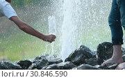 Купить «A man tries to fill the bottle with a water from underground fountain coming between the rocks», видеоролик № 30846590, снято 4 апреля 2020 г. (c) Константин Шишкин / Фотобанк Лори
