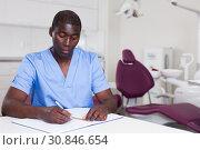 Confident male dentist working with medical records in dental office. Стоковое фото, фотограф Яков Филимонов / Фотобанк Лори