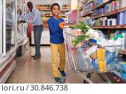 Купить «Nice African American boy carrying purchases», фото № 30846738, снято 15 апреля 2019 г. (c) Яков Филимонов / Фотобанк Лори