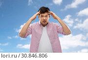 Купить «man touching his head over blue sky background», фото № 30846806, снято 3 февраля 2019 г. (c) Syda Productions / Фотобанк Лори