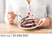 Купить «woman eating piece of layer cake with cherry», фото № 30846866, снято 21 мая 2015 г. (c) Syda Productions / Фотобанк Лори