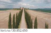 Купить «A view of the road between the coniferous trees. At the end of the road is a house. Drone rises. Italy, Toskana.», видеоролик № 30852650, снято 27 мая 2020 г. (c) Константин Шишкин / Фотобанк Лори