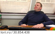 Tired employee leaned back in his chair in the workplace. Стоковое видео, видеограф Aleksandr Sulimov / Фотобанк Лори