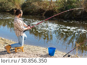 Купить «Adult man standing near river and pulling fish expressing emotions of dedication», фото № 30856350, снято 15 марта 2019 г. (c) Яков Филимонов / Фотобанк Лори