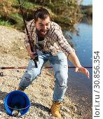 Купить «Adult man standing near river and pulling fish expressing emotions of dedication», фото № 30856354, снято 15 марта 2019 г. (c) Яков Филимонов / Фотобанк Лори