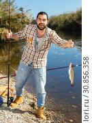 Купить «Adult man standing near river and pulling fish expressing emotions of dedication», фото № 30856358, снято 15 марта 2019 г. (c) Яков Филимонов / Фотобанк Лори