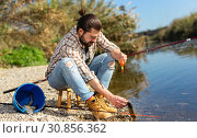 Positive fisherman holding catch freshwater fish in hands. Стоковое фото, фотограф Яков Филимонов / Фотобанк Лори