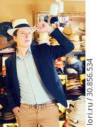 Купить «portrait of smiling guy try on bucket hat at store», фото № 30856534, снято 2 мая 2017 г. (c) Яков Филимонов / Фотобанк Лори