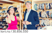 Купить «Positive woman and man trying on fashion hats», фото № 30856550, снято 2 мая 2017 г. (c) Яков Филимонов / Фотобанк Лори