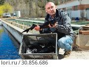 Купить «Man demonstrating freshly caught fish», фото № 30856686, снято 19 марта 2019 г. (c) Яков Филимонов / Фотобанк Лори