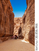 Tourists in narrow passage of rocks of Petra canyon in Jordan. Petra has been a UNESCO World Heritage Site since 1985. Way through Siq gorge to stone city Petra (2012 год). Редакционное фото, фотограф Наталья Волкова / Фотобанк Лори