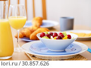 Close up fresh healthy nutritious breakfast jug glass with orange natural juice croissants on background, bowl plate with porridge or cereals garnished cherry, kiwi, orange slices on wicker place mat. Стоковое фото, фотограф Alexander Tihonovs / Фотобанк Лори