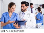 Купить «Doctor with younger female colleague», фото № 30859830, снято 25 мая 2020 г. (c) Яков Филимонов / Фотобанк Лори