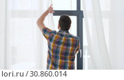 Купить «man opening window curtain raising arms at home», видеоролик № 30860014, снято 24 мая 2019 г. (c) Syda Productions / Фотобанк Лори