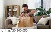 Купить «smiling man unpacking takeaway food at home», видеоролик № 30860050, снято 24 мая 2019 г. (c) Syda Productions / Фотобанк Лори