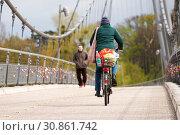 Eine Radfahrerin und ein Fußgänger auf einer Hängebrücke über den Fluss Elbe in Magdeburg. Die Brücke wurde im Jahre 1999 anlässlich der Bundesgartenschau in Magdeburg gebaut. Стоковое фото, фотограф Zoonar.com/Heiko Kueverling / age Fotostock / Фотобанк Лори