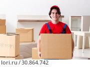 Купить «Young male contractor with boxes working indoors», фото № 30864742, снято 1 февраля 2019 г. (c) Elnur / Фотобанк Лори