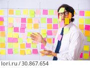 Купить «Young employee in conflicting priorities concept», фото № 30867654, снято 16 октября 2018 г. (c) Elnur / Фотобанк Лори
