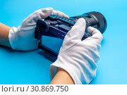 Купить «Top view female hand wearing white gloves holding professional camera», фото № 30869750, снято 16 июля 2020 г. (c) Pavel Biryukov / Фотобанк Лори