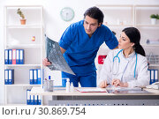Купить «Two young doctors working in the clinic», фото № 30869754, снято 25 января 2019 г. (c) Elnur / Фотобанк Лори