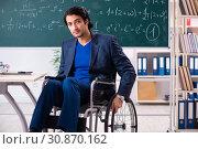 Купить «Young handsome man in wheelchair in front of chalkboard», фото № 30870162, снято 23 ноября 2018 г. (c) Elnur / Фотобанк Лори