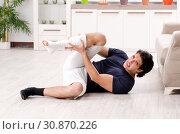 Купить «Leg injured young man suffering at home», фото № 30870226, снято 15 января 2019 г. (c) Elnur / Фотобанк Лори