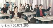 Купить «Adult people raising hands in classroom», фото № 30871286, снято 8 мая 2018 г. (c) Яков Филимонов / Фотобанк Лори