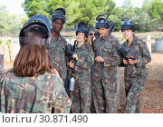 Купить «Four beginners attentively listening instruction about marker gun before paintball match from female trainer», фото № 30871490, снято 11 августа 2018 г. (c) Яков Филимонов / Фотобанк Лори