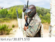 Купить «African-American paintball player wearing protective helmet and camouflage standing outdoors with marker gun after game», фото № 30871510, снято 11 августа 2018 г. (c) Яков Филимонов / Фотобанк Лори