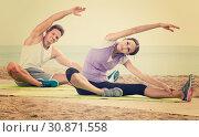 Купить «Smiling woman and guy training on beach by sea», фото № 30871558, снято 26 июня 2019 г. (c) Яков Филимонов / Фотобанк Лори