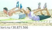Купить «Active guy and girl training on beach by sea», фото № 30871566, снято 26 июня 2019 г. (c) Яков Филимонов / Фотобанк Лори
