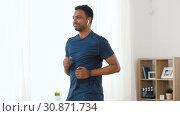Купить «man with wireless earphones exercising at home», видеоролик № 30871734, снято 27 мая 2019 г. (c) Syda Productions / Фотобанк Лори