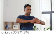 Купить «man with fitness tracker stretching waist at home», видеоролик № 30871746, снято 27 мая 2019 г. (c) Syda Productions / Фотобанк Лори