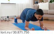 Купить «man with fitness tracker doing plank at home», видеоролик № 30871750, снято 27 мая 2019 г. (c) Syda Productions / Фотобанк Лори