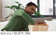 Купить «smiling indian man unpacking takeaway food at home», видеоролик № 30871766, снято 27 мая 2019 г. (c) Syda Productions / Фотобанк Лори