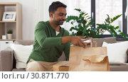 Купить «smiling indian man unpacking takeaway food at home», видеоролик № 30871770, снято 27 мая 2019 г. (c) Syda Productions / Фотобанк Лори