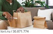Купить «african man unpacking takeaway food at home», видеоролик № 30871774, снято 27 мая 2019 г. (c) Syda Productions / Фотобанк Лори
