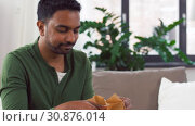 Купить «indian man unpacking takeaway food at home», видеоролик № 30876014, снято 27 мая 2019 г. (c) Syda Productions / Фотобанк Лори