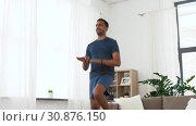 Купить «indian man jumping on spot at home», видеоролик № 30876150, снято 27 мая 2019 г. (c) Syda Productions / Фотобанк Лори