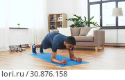 Купить «man with fitness tracker doing plank at home», видеоролик № 30876158, снято 27 мая 2019 г. (c) Syda Productions / Фотобанк Лори