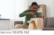 smiling indian man unpacking takeaway food at home. Стоковое видео, видеограф Syda Productions / Фотобанк Лори