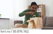 Купить «smiling indian man unpacking takeaway food at home», видеоролик № 30876162, снято 27 мая 2019 г. (c) Syda Productions / Фотобанк Лори