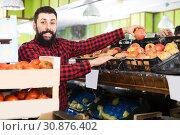 Купить «Male seller offering pomegranates in shop», фото № 30876402, снято 15 ноября 2016 г. (c) Яков Филимонов / Фотобанк Лори