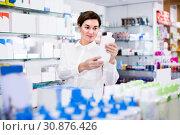 Купить «Woman 25-35 years old is browsing rows of body care products», фото № 30876426, снято 31 января 2017 г. (c) Яков Филимонов / Фотобанк Лори