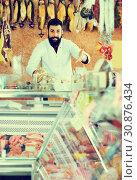 Купить «Smiling male seller grouping meat to sell», фото № 30876434, снято 16 ноября 2016 г. (c) Яков Филимонов / Фотобанк Лори
