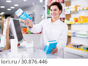 Купить «Pharmacist ready to assist in choosing at counter», фото № 30876446, снято 31 января 2017 г. (c) Яков Филимонов / Фотобанк Лори