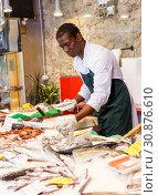 Купить «Salesman preparing fish for sale», фото № 30876610, снято 17 октября 2018 г. (c) Яков Филимонов / Фотобанк Лори