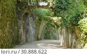 Купить «Picturesque alley with stone arches in park of Quinta da Regaleira, Sintra, Portugal», видеоролик № 30888622, снято 14 мая 2019 г. (c) Яков Филимонов / Фотобанк Лори