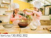 Купить «Little sisters cooks in caps kneads eggs in a bow», фото № 30892302, снято 30 марта 2019 г. (c) Tryapitsyn Sergiy / Фотобанк Лори