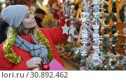 Купить «Happy girl chooses Christmas toys on the street market», видеоролик № 30892462, снято 18 декабря 2018 г. (c) Яков Филимонов / Фотобанк Лори